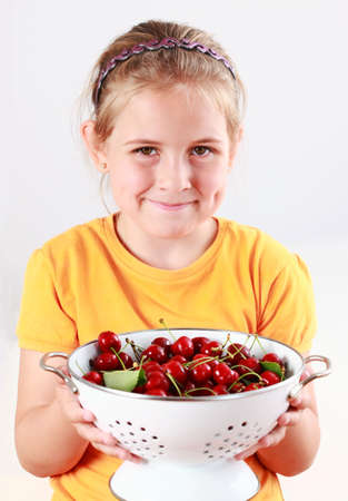 Cute child holding a bowl of fresh cherries photo