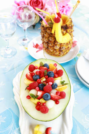 Delicious fresh fruit salad served in melon bowl as dessert photo