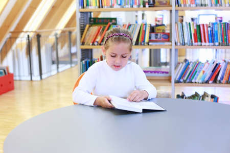 School girl reading a book in library Stock Photo - 10020651