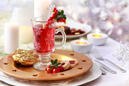 Hot wine cranberry punch for winter and Christmas and Christmas tree in background photo