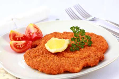 schnitzel: Delicious Wiener Schnitzel with lemon and tomatoes Stock Photo