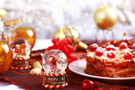Christmas table setting with Charlotte cake with small snow globe photo
