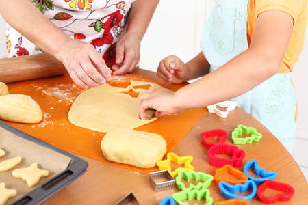 Detail of hands cutting pastry - child and adult photo