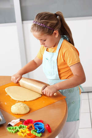 kneading: Cute girl baking cookies for Christmas