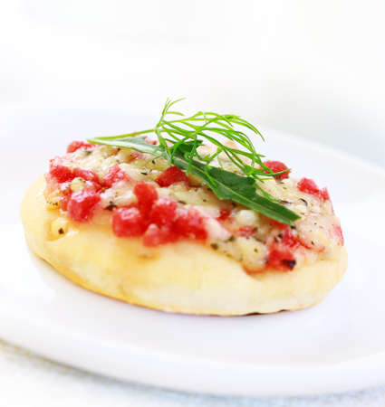cheesy: Small cheesy cakes with ham and rocket as appetizer on white plate