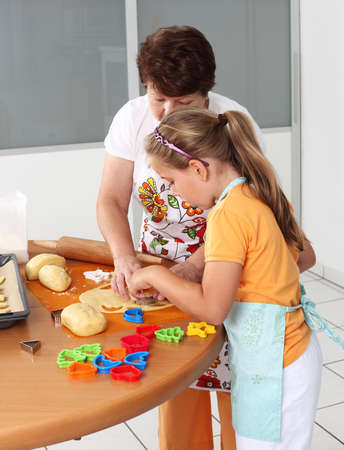 Child and senior woman cutting pastry for Christmas Stock Photo - 10686052