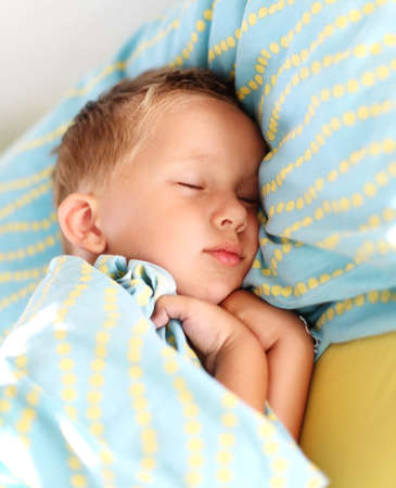 enfant qui dort: Petit garçon dormant paisiblement dans son lit