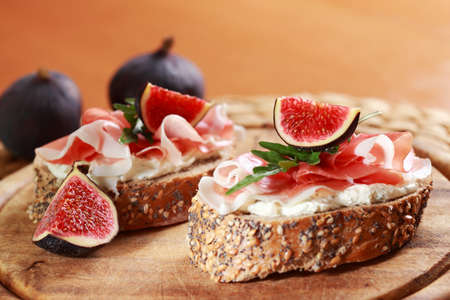 mediterranean cuisine: Sandwich with cream cheese, prosciutto, fig and rocket