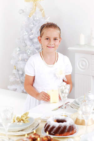 Cute girl setting table for Christmas photo