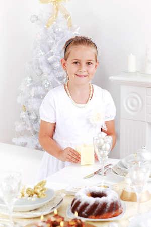 Cute girl setting table for Christmas photo