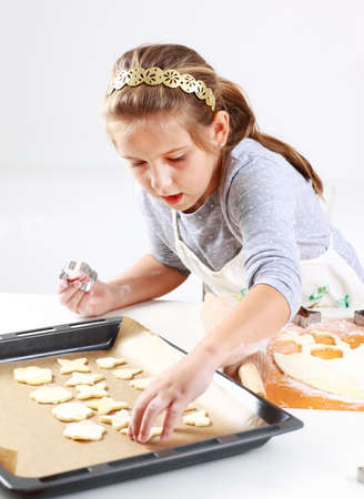cookie cutters: Cute girl baking cookies for Christmas