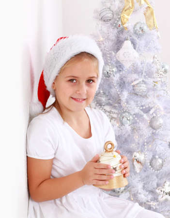Girl holding bell with Christmas tree in background photo