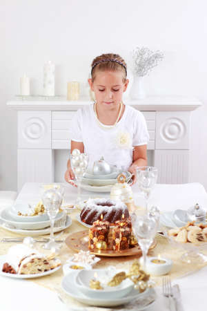 setting table: Cute girl setting table for Christmas