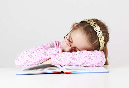 Tired schoolgirl sleeping on book instead of learning photo