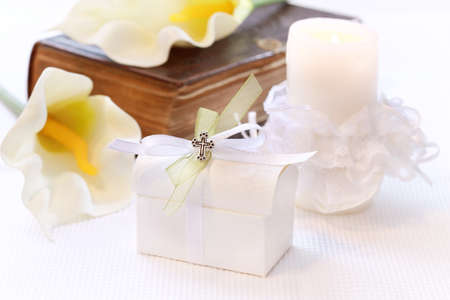 confirmation: First holy communion or confirmation - candle, open bible and small present Stock Photo