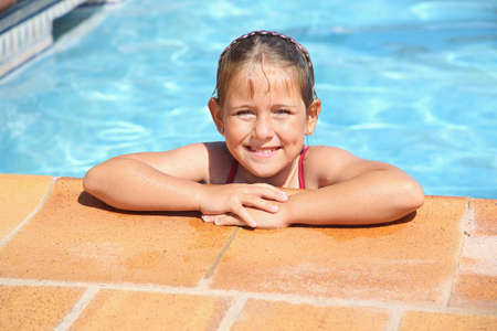 Happy girl smiling at swimming pool photo