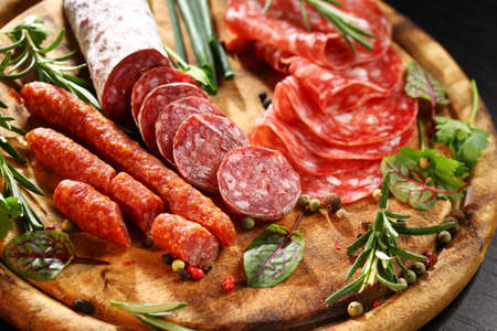 Different Italian ham and salami with herbs photo