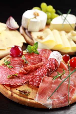 salami: Salami y tabla de quesos con verduras y hierbas Foto de archivo