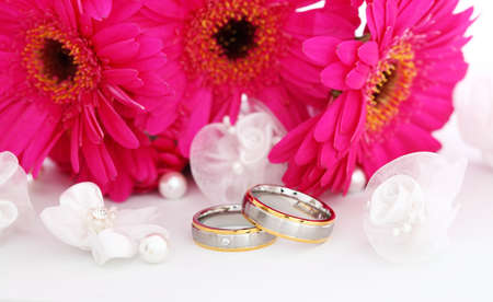 Wedding still life with beautiful golden rings and bouquet in background photo