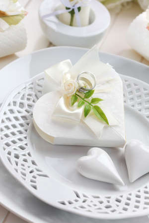 Luxury place setting in white with small present for the guests photo