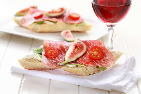 Baguette with lettuce, salami and fresh figs photo