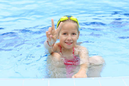 Cute girl with goggles in swimming pool showing victory sign photo