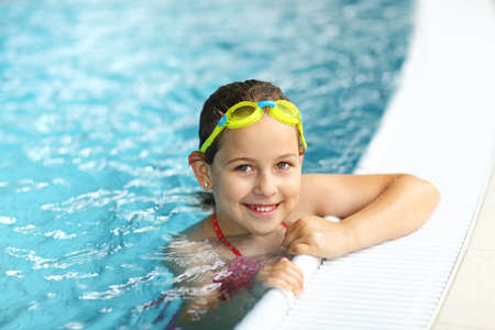 kids swimming pool: Cute girl with goggles in swimming pool