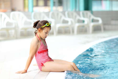 Cute child with goggles relaxing by swimming pool photo