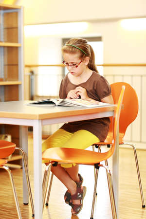 School girl studying in library photo
