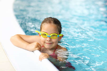 Cute girl with goggles in swimming pool photo