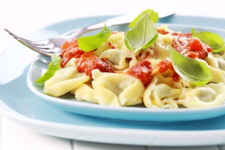 Tortellini with tomato sauce and cheese, fresh basil photo
