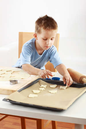 Small boy baking cookies for Christmas photo