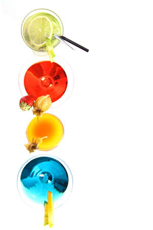 Different cocktails or longdrinks garnished with fruits on white background