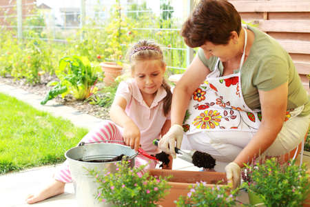 Elderly woman and child replanting flowers for better growth Standard-Bild