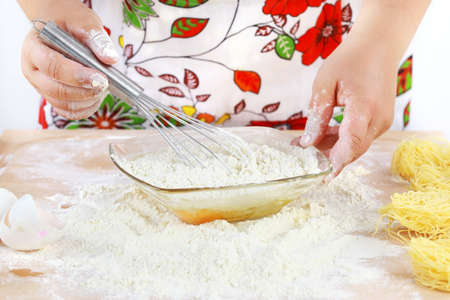 Details of womans hands mixing  dough photo