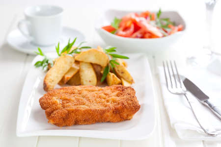 Schnitzel with wedges and tomato salad photo
