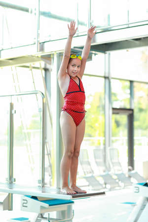 Child on diving board ready for jumping photo