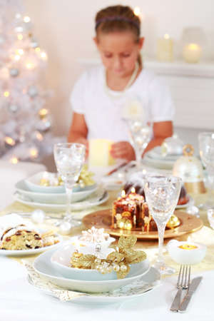 Luxury Christmas place setting with helping child in background photo
