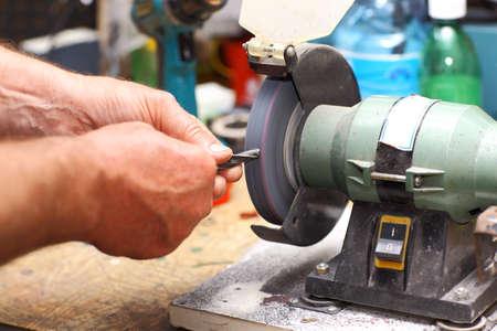 Detail of hands working on sharpening machine tool photo