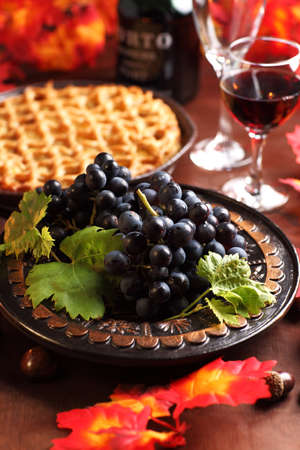 Fresh grapes and glass of wine with apple pie for Thanksgiving