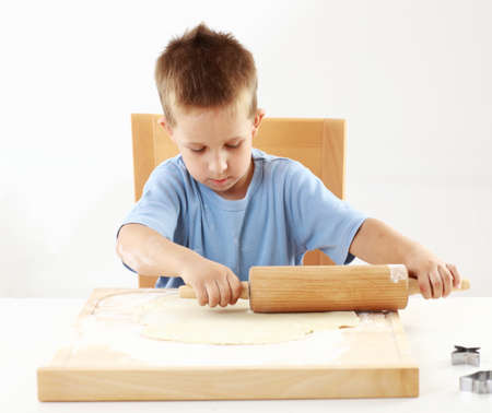 Small boy helping in the kitchen - rolling dough for Christmas cookies Stock Photo - 15256301