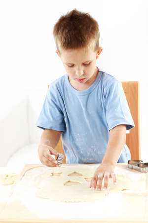 Small boy cutting cookies for Christmas Stock Photo - 15256305