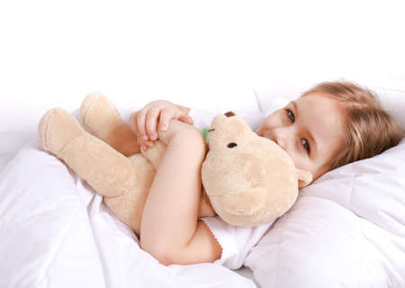 Cute girl cuddling with teddy bear to sleep
