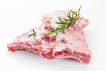 barbecue ribs: Costillas de cerdo sin procesar con romero en el fondo blanco Foto de archivo