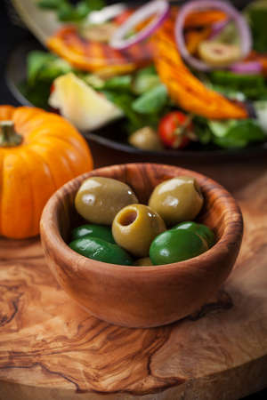 Delicious green olives in the bowl with salad photo