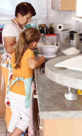 Senior woman and child baking together photo