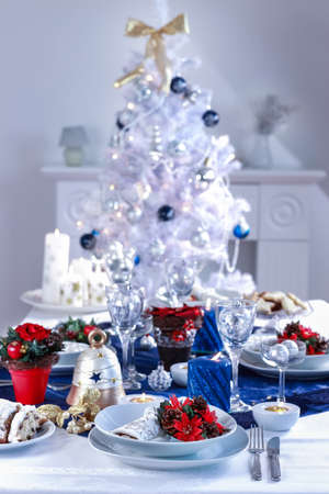Place setting for Christmas in white and blue with the tree photo