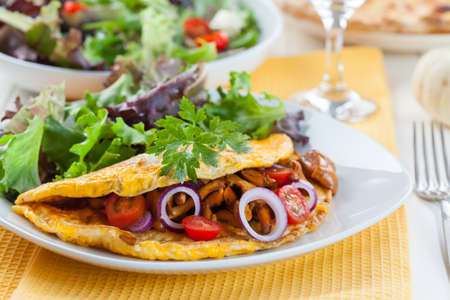 Omelet filled with chanterelle mushrooms and vegetable salad