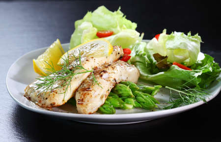 seafood salad: Delicious fried fish on green asparagus with salad