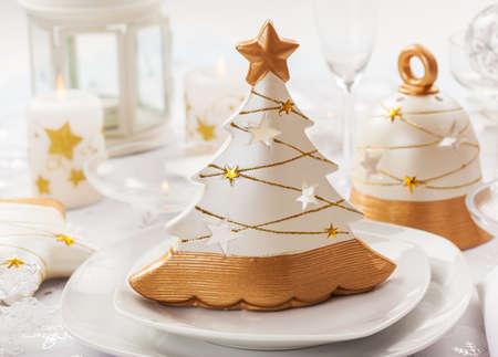 weihnachtskuchen: Festlich gedeckter Tisch zu Weihnachten mit kleinen Baum in weißen und goldenen Tönen